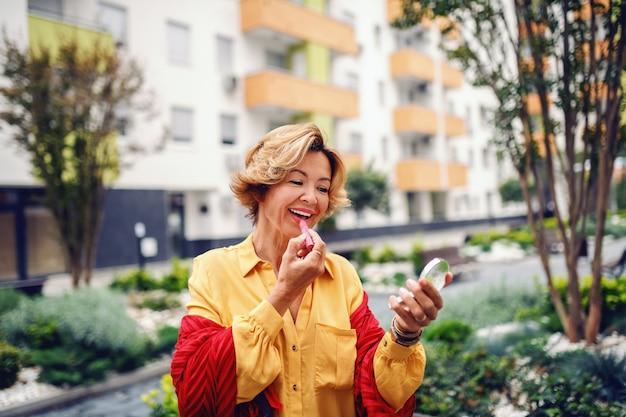 Portret pięknej kaukaskiej blondynki starszej kobiety trzymającej lustro i stawiając szminkę stojąc w parku.