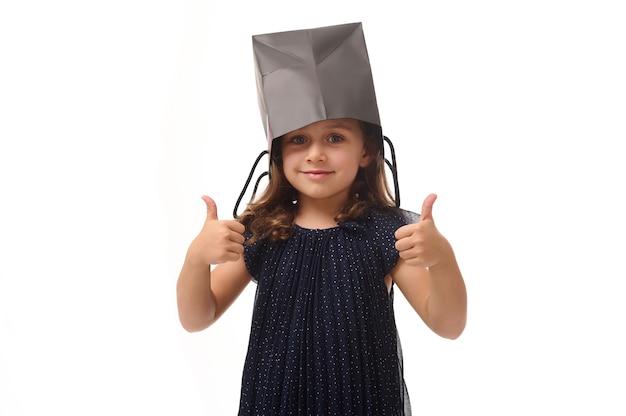 Portret pięknej kaukaskiej córeczki zabawy, kładąc na głowie czarny pakiet zakupów, patrząc na kamerę, pokazując kciuk do góry palcami. koncepcja czarnego piątku