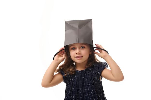 Portret pięknej kaukaskiej europejskiej dziewczyny bawiącej się, kładącej czarną paczkę na zakupy na głowie, patrzącej na kamerę, odizolowanej na różowym tle z kopią przestrzeni, koncepcja czarnego piątku