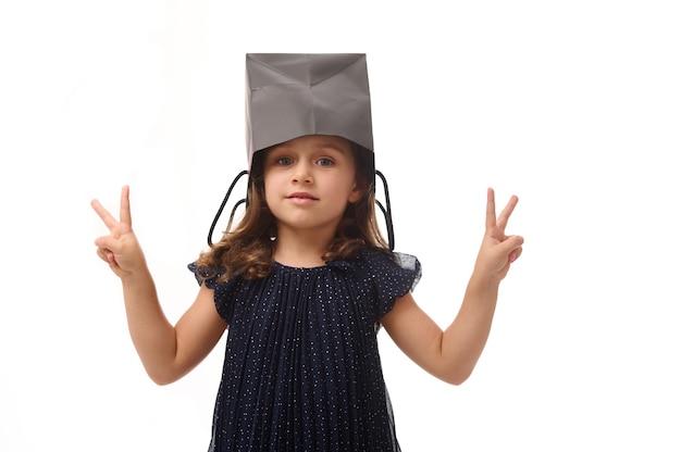 Portret pięknej kaukaskiej europejskiej dziewczyny bawiącej się, kładącej na głowie czarną paczkę z zakupami, patrzącej w kamerę, pokazującej palcami znak pokoju. koncepcja czarnego piątku
