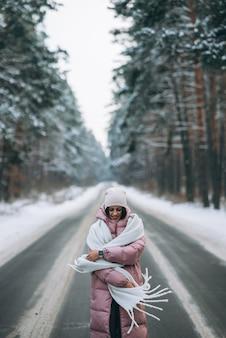 Portret pięknej kaukaskiej kobiety na drodze przez zaśnieżony las