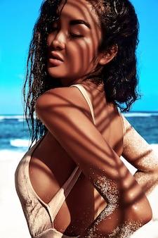 Portret pięknej kaukaskiej opalonej modelki z ciemnymi długimi włosami w beżowym stroju kąpielowym pozowanie na letniej plaży z białym piaskiem na błękitnym niebie i oceanie