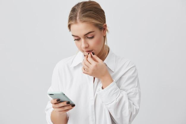 Portret pięknej kaukaskiej studentki ubrany od niechcenia, trzymając telefon komórkowy, komunikując się z przyjaciółmi za pośrednictwem sieci społecznościowych, używając połączenia z internetem, dotykając jej ust.