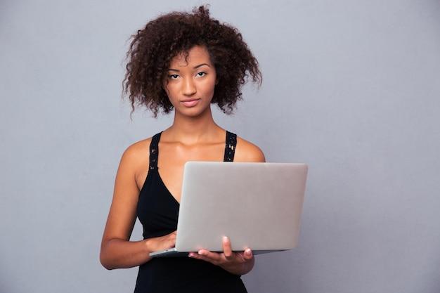 Portret pięknej kobiety afro american za pomocą laptopa na szarej ścianie. patrząc z przodu