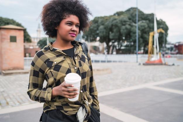 Portret pięknej kobiety afro amerykański łacińskiej trzymając filiżankę kawy na zewnątrz na ulicy. koncepcja miejska.
