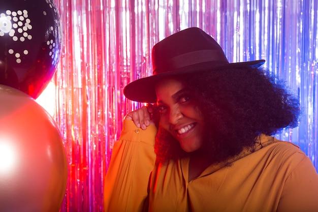 Portret pięknej kobiety afroamerykanów przed migotliwym tle. przyjęcie urodzinowe