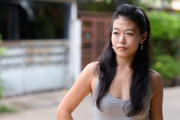 Portret pięknej kobiety azjatyckich myślenia i odwracając