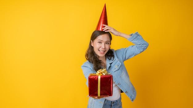 Portret pięknej kobiety azji umieścić czerwony kapelusz na głowie, trzymając pudełko