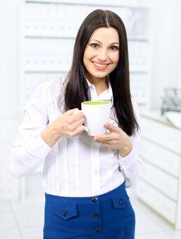 Portret pięknej kobiety biznesu trzymającej filiżankę kawy