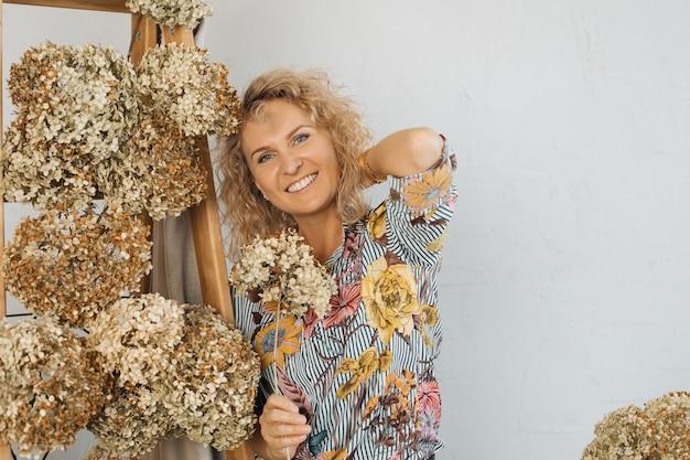 Portret pięknej kobiety blondynka, kwiaciarnia dekorator wnętrz, uśmiechając się, patrząc w ramkę. miejsce na kopię. koncepcja naturalnego wystroju jesienią.