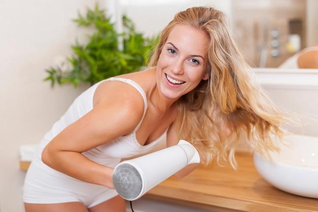 Portret pięknej kobiety blondynka, suszenie włosów w łazience