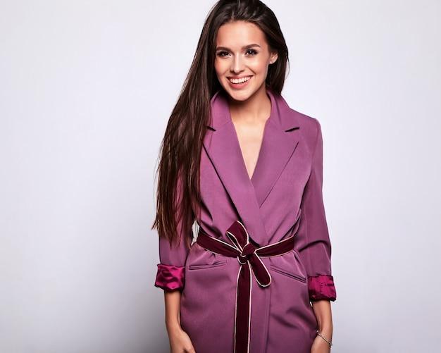 Portret pięknej kobiety brunetka model w różowym stroju bez makijażu na szarym tle