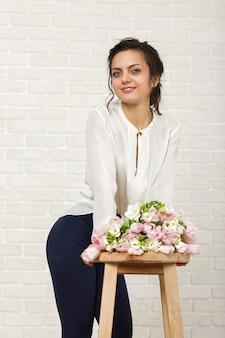 Portret pięknej kobiety brunetka z bukietem kwiatów tulipanów