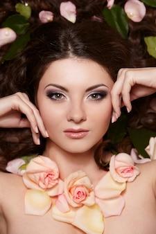 Portret pięknej kobiety brunetka z długie kręcone włosy i jasny makijaż witjh kwiaty we włosach
