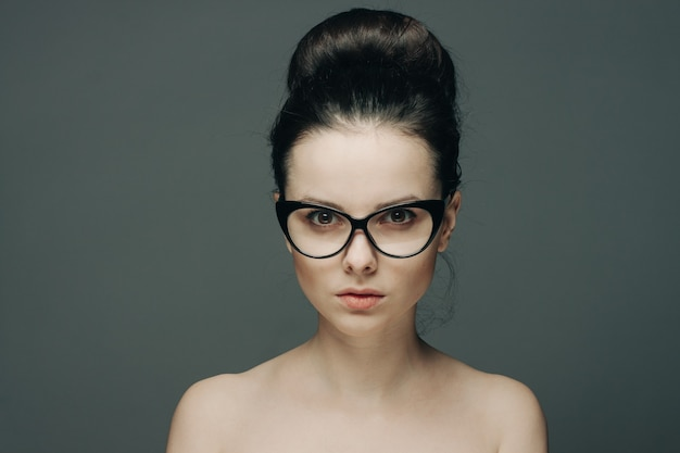 Portret pięknej kobiety brunetka z gołymi ramionami modny model fryzury