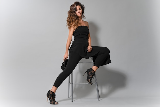 Portret pięknej kobiety brunetka z ładnym uśmiechem ubrany w czarne ubrania, siedząc