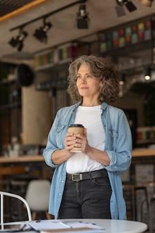 Portret pięknej kobiety, ciesząc się filiżanką kawy