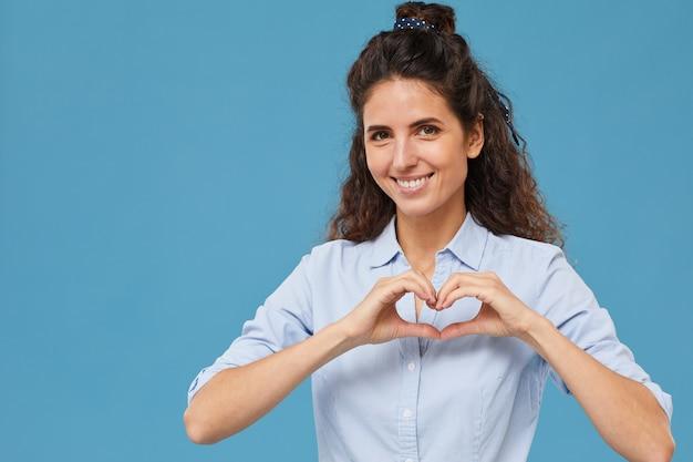 Portret pięknej kobiety co kształt serca z jej rąk i uśmiechnięty na białym tle na niebieskim tle