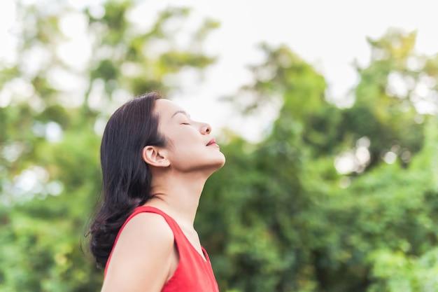 Portret pięknej kobiety czującej żywą, oddychającą świeżym powietrzem z zamkniętymi oczami