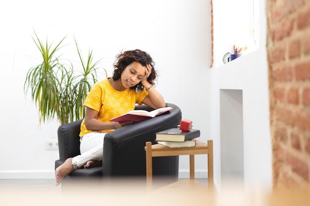 Portret pięknej kobiety, czytając książkę w domu. miejsce na tekst.