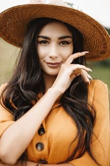 Portret pięknej kobiety długie ciemne włosy w kapeluszu patrząc na kamery uśmiechnięty, dotykając jej twarzy ręką na zewnątrz w przyrodzie.
