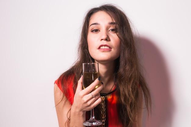 Portret pięknej kobiety doceniają. wakacyjny styl życia na białym tle. modelka w czerwonej sukience z lampką wina.