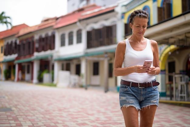 Portret pięknej kobiety dojrzałe turystyczne cieszyć się życiem podczas podróży w singapurze