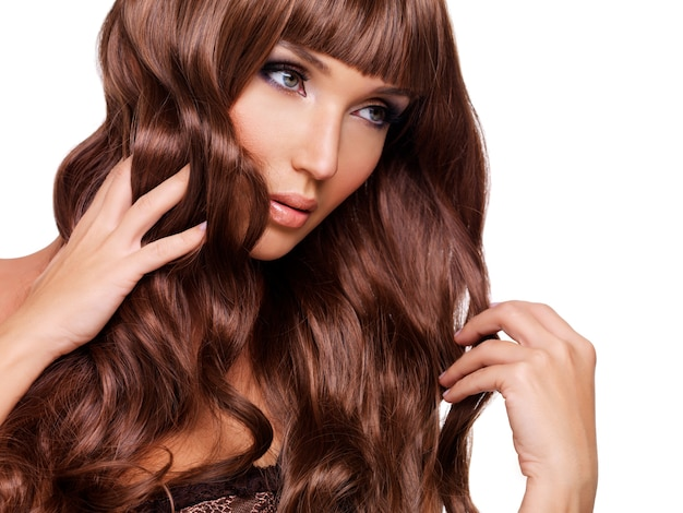 Portret pięknej kobiety dorosłych z długimi rudymi włosami. zbliżenie twarzy z kręconymi fryzurami, na białym tle.