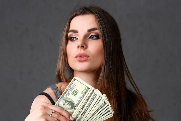 Portret pięknej kobiety europejskiej. rozrzucone banknoty w dolarach w modnych ślubach stylizują kręcone włosy z białym, blokującym widok kamery okiem