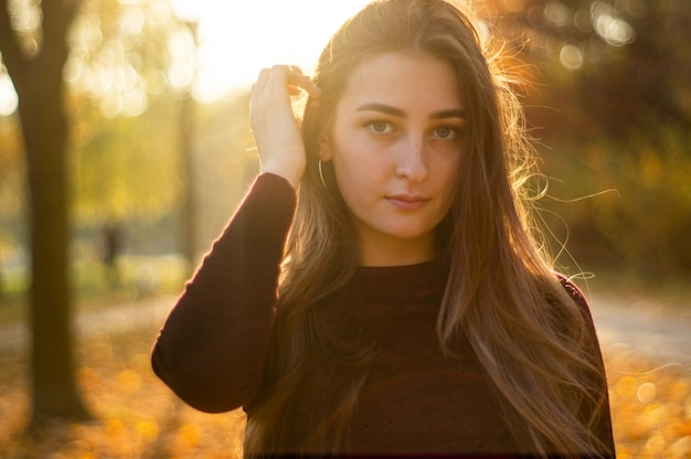 Portret pięknej kobiety i patrząc od parku podczas zachodu słońca
