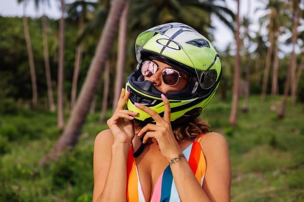 Portret pięknej kobiety jeźdźca w żółto-zielonym kasku motocyklowym i kolorowej lekkiej letniej sukience w dżungli na tropikalnym polu pod palmami.