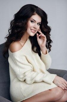 Portret pięknej kobiety. kobieta w zimowy sweter i piękne kręcone włosy.