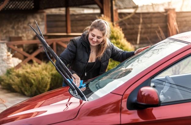 Portret pięknej kobiety myjącej przednią szybę samochodu