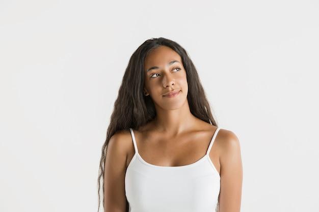 Portret pięknej kobiety na białym tle na białej ścianie