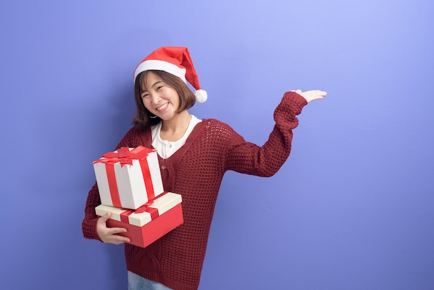 Portret pięknej kobiety na sobie czerwony kapelusz świętego mikołaja, trzymając pudełko na tle studio, koncepcja bożego narodzenia i nowego roku
