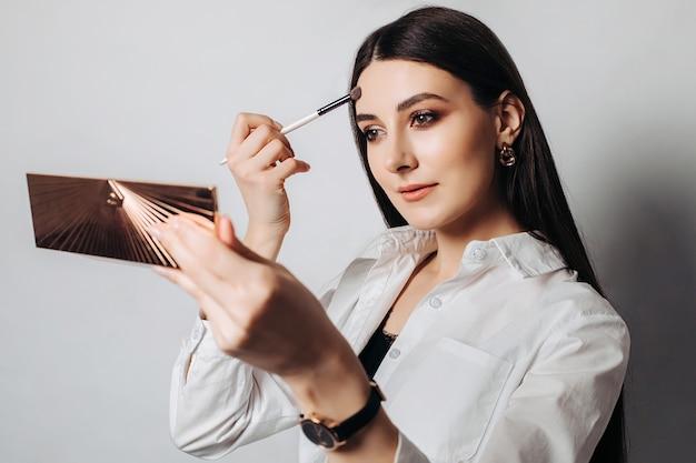 Portret pięknej kobiety nakładającej na siebie makijaż, patrząc w lustro na białej ścianie.
