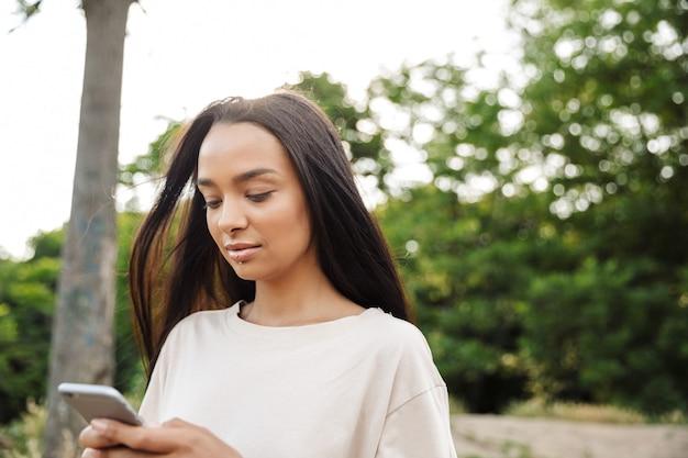 Portret pięknej kobiety noszącej przekłuwanie warg trzymającej smartfona podczas spaceru w zielonym parku