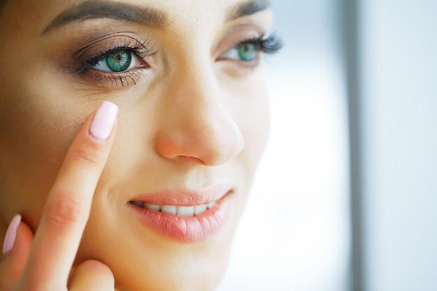 Portret pięknej kobiety o zielonych oczach i soczewkach kontaktowych.