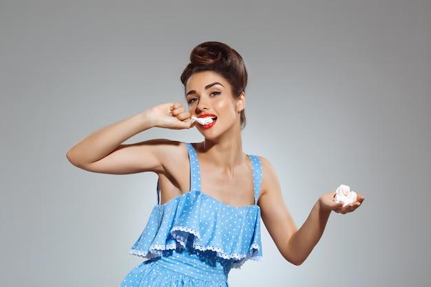 Portret pięknej kobiety pin-up jedzenia słodyczy