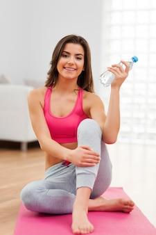 Portret pięknej kobiety po treningu z butelką wody