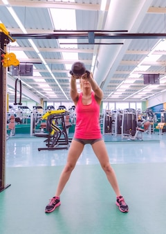 Portret pięknej kobiety podnoszenia czarnego żelaza kettlebell w treningu crossfit na centrum fitness