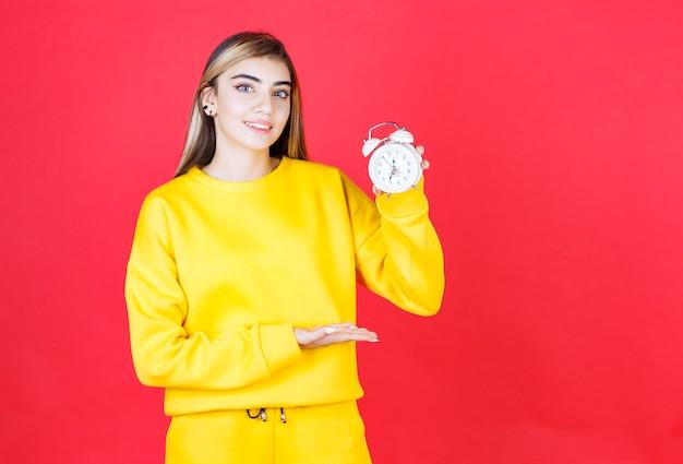 Portret pięknej kobiety pokazujący mały zegar na czerwonej ścianie