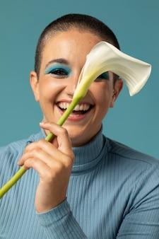 Portret pięknej kobiety pozującej w golfie z kwiatkiem
