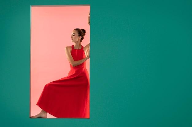 Portret pięknej kobiety pozującej w lejącej się czerwonej sukience z miejscem na kopię