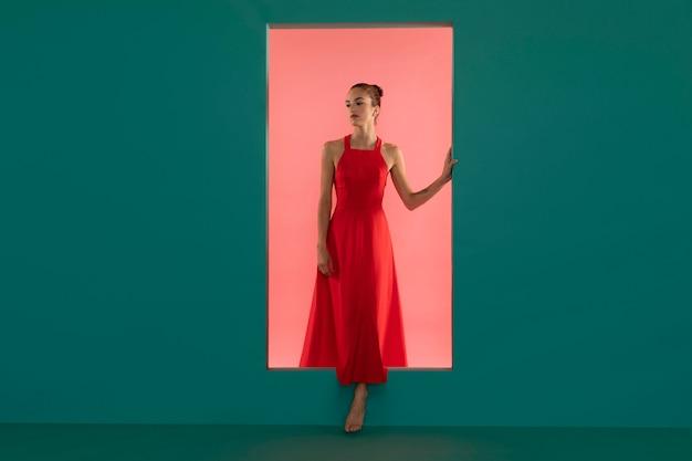 Portret pięknej kobiety pozującej w lejącej się czerwonej sukience