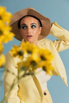 Portret pięknej kobiety pozującej w żółtej kurtce i kwiatach