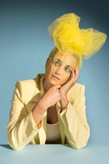 portret pięknej kobiety pozującej z awangardowym nakryciem głowy