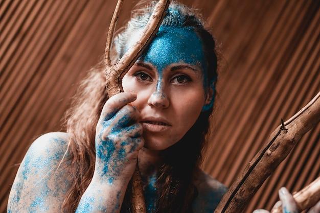 Portret pięknej kobiety pozuje jak w dzikim lesie. kobieta z błękitem błyszczy na jej twarzy. ludzie różnią się od innych. indywidualność