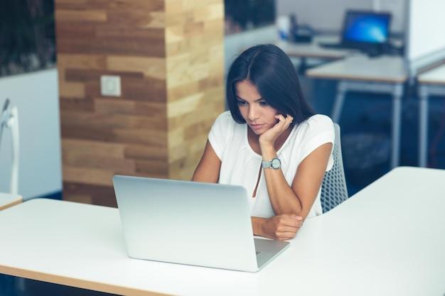 Portret pięknej kobiety pracującej na laptopie w biurze