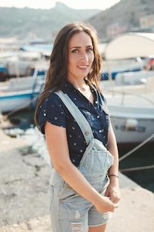 Portret pięknej kobiety przed drewnianym molo i jachtów